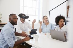 Man in VR goggles at a desk with colleagues in an office stock image
