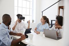 Man in VR goggles at a desk watched by colleagues in office Royalty Free Stock Photo
