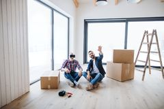A man with VR goggles and his senior father furnishing new house, a new home concept. royalty free stock image