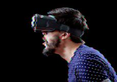 Man with VR goggles over digital glitch effects Stock Photography