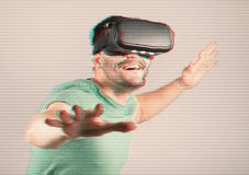 Man with VR goggles over digital glitch effects Stock Photo