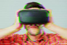 Man with VR goggles over digital glitch effects Royalty Free Stock Images
