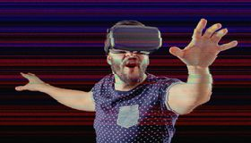 Man with VR goggles over digital glitch effects Stock Images
