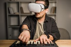 Man in vr goggles using MPC pad. Impressed young man in vr goggles using MPC pad royalty free stock photo