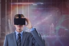 Man in VR headset looking against galaxy and city background Stock Image
