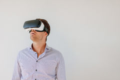 Man with VR headset looking away at the objects. Shot of young man in VR headset looking away at the objects in virtual reality. Caucasian male with virtual Stock Photo