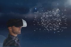Man in VR headset looking at interface against sky with flares Stock Photos