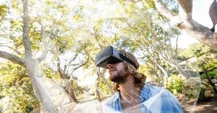 Man in VR headset looking at interface. Digital composite of Man in VR headset looking at interface Royalty Free Stock Photography