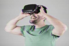 Man in VR-headset over glitch effect Stock Photos