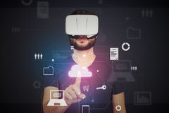 Man in VR-headset pressing icon on imaginary interactive monito Stock Photo