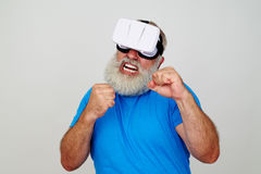 Man in VR-headset standing in fighting pose with clenched fists Royalty Free Stock Image