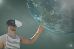 Man in VR headset touching 3D planet against green background with flares. Digital composite of Man in VR headset touching 3D planet against green background stock photos