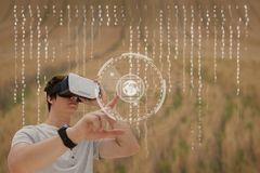 Man in VR headset touching interface against field background with interface. Digital composite of Man in VR headset touching interface against field background stock images