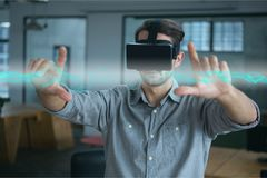 Man in VR headset touching interface with flare. Digital composite of Man in VR headset touching interface with flare Stock Photo