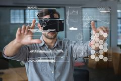 Man in VR headset touching interfaces. Digital composite of Man in VR headset touching interfaces Stock Photo