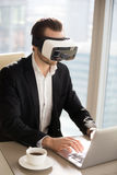 Man in VR headset typing on laptop at workplace. Man in VR headset typing text on laptop at desk in office. Businessman working on computer with virtual reality Royalty Free Stock Photography