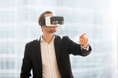 Man in VR headset using augmented reality in work. Businessman in VR headset working in office augmented reality. Man using virtual reality glasses to interact Royalty Free Stock Image
