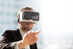 Man in VR headset using gestures in simulation. Businessman pointing in air in virtual reality glasses on head. Man in VR headset using gestures in app virtual Royalty Free Stock Photos