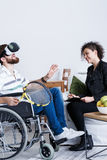 Man in VR with tennis racket. Bearded men on wheelchair in VR goggles with tennis racket during therapy stock images