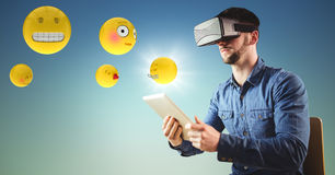 Man in VR using tablet with emojis and flare against blue green background Royalty Free Stock Photography