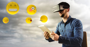 Man in VR using tablet with emojis and flare against cloudy sky Royalty Free Stock Image
