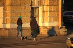 Man, vrouw, en hond die de straat reduceren stock foto