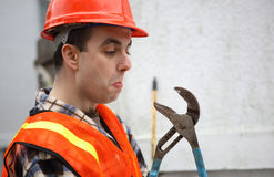Man vs. Tool. Humorous image of a construction worker looking at an open pipe wrench tool. It looks like tool wants to attack and bite him Stock Images