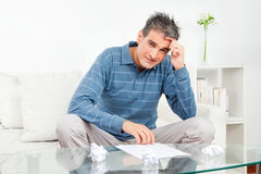 Man with wadded paper balls on. Pensive man with some wadded paper balls on living room table Royalty Free Stock Photography