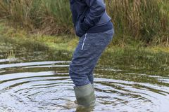 Man wadding through water wearing wellington boots Stock Photo