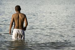 Man wading in lake or sea. Rear view of young man wading in sea or lake Stock Images