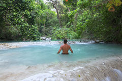 Man wading in tropical paradise pool. Muscular Caucasian man wading away from camera in exotic turquoise blue pool in lush tropical rainforest above La Conchuda Stock Photos