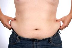Man Waist Fat. Overweight man pinches the excess fat that he has around his waist Royalty Free Stock Photos