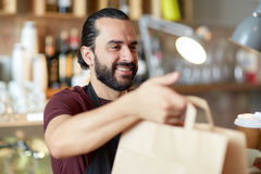 Man or waiter with coffee and paper bag at bar Royalty Free Stock Photo