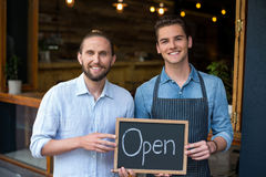 Man and waiter holding chalkboard with open sign Royalty Free Stock Photo
