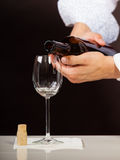 Man waiter pouring white wine into glass. Male waiter or butler serving pouring white wine into glass Stock Photo