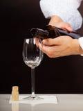 Man waiter pouring white wine into glass. Stock Photo