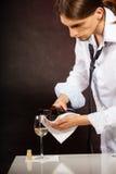 Man waiter pouring white wine into glass. Stock Photos