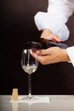 Man waiter pouring white wine into glass. Male waiter or butler serving pouring white wine into glass Stock Photography