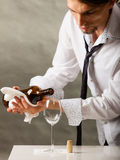 Man waiter pouring wine into glass. Male waiter or butler serving pouring wine into glass Royalty Free Stock Photo