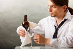 Man waiter pouring wine into glass. Male waiter or butler serving pouring wine into glass Royalty Free Stock Images