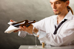 Man waiter pouring wine into glass. Stock Images