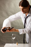 Man waiter pouring wine into glass. Royalty Free Stock Photo