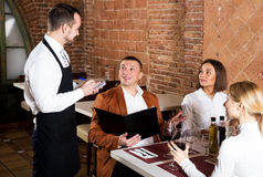 Man waiter receiving order from guests. Smiling young men waiter receiving order from guests in country restaurant Royalty Free Stock Photography