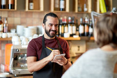 Man or waiter serving customer at bar. Small business, people and service concept - happy men or waiter with notebook and pencil serving customer at coffee shop Royalty Free Stock Photos