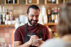Man or waiter serving customer at bar. Small business, people and service concept - happy man or waiter with notebook and pencil serving customer at coffee shop Royalty Free Stock Photography