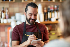 Man or waiter serving customer at bar. Small business, people and service concept - happy man or waiter with notebook and pencil serving customer at coffee shop Royalty Free Stock Image