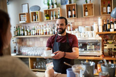 Man or waiter serving customer at coffee shop. Small business, people and service concept - happy men or waiter with coffee cup serving customer giving him money Stock Photography