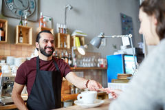 Man or waiter serving customer at coffee shop. Small business, people and service concept - happy men or waiter with coffee cup serving customer giving him money Royalty Free Stock Image