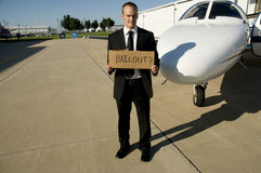Man waiting for a bailout in front of a corporate. Man holding a cardboard sign that says bailout standing in front of a private corportate jet Royalty Free Stock Image