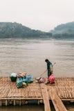 Man Waiting Boat for Moving Commodities in The River at Luang Prabang, Laos.  stock photo